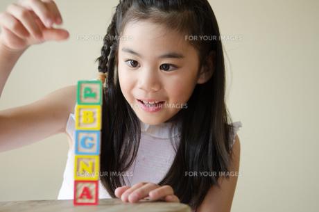 アルファベットの積み木で遊ぶ女の子の素材 [FYI01077533]