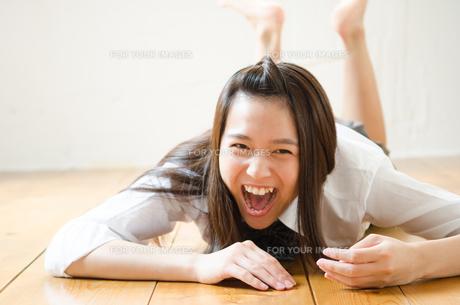 床に寝転んで大笑いする制服姿の女性の素材 [FYI01077541]