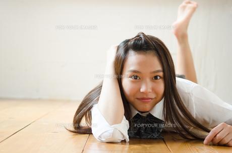 床に寝転んでいる制服姿の女性の素材 [FYI01077542]