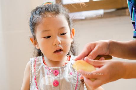 包丁でりんごを切っている手元を見ている女の子の素材 [FYI01077563]