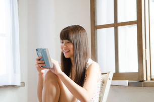 イスに座ってスマートフォンを操作する女性の素材 [FYI01077576]