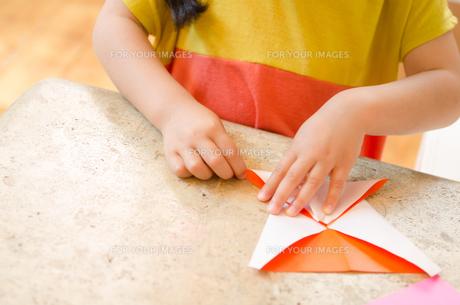 折り紙をしている女の子の手の素材 [FYI01077578]