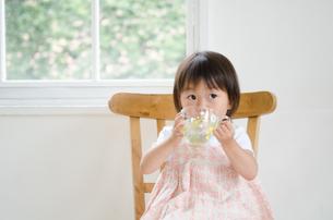 イスに座って水を飲んでいる女の子の素材 [FYI01077586]