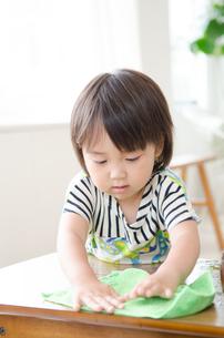 机の上を拭いている男の子の素材 [FYI01077590]