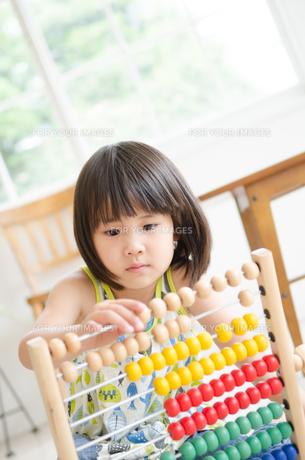 100玉そろばんで遊んでいる女の子の素材 [FYI01077592]