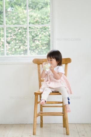 イスに座って水を飲んでいる女の子の素材 [FYI01077593]