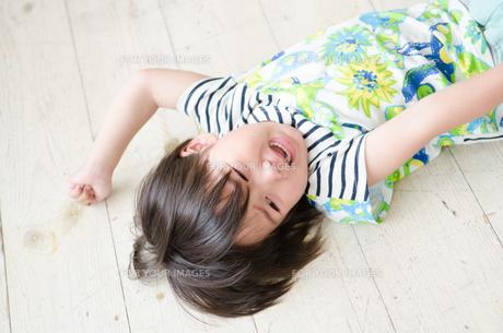 床に転がって泣いている男の子の素材 [FYI01077595]