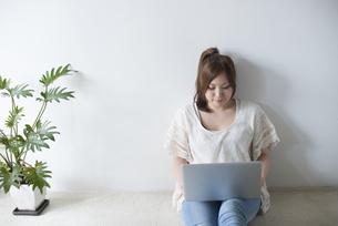 床に座ってノートパソコンを操作する女性の素材 [FYI01077600]