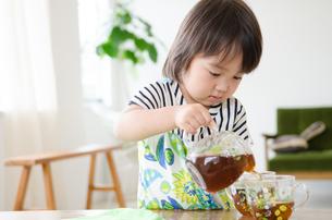 麦茶をついでいる男の子の素材 [FYI01077604]