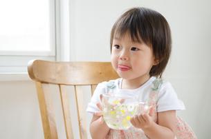 イスに座って水の入ったカップを持っている女の子の素材 [FYI01077605]