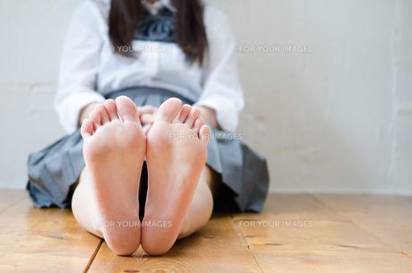床に座っている制服姿の女性の足の素材 [FYI01077615]