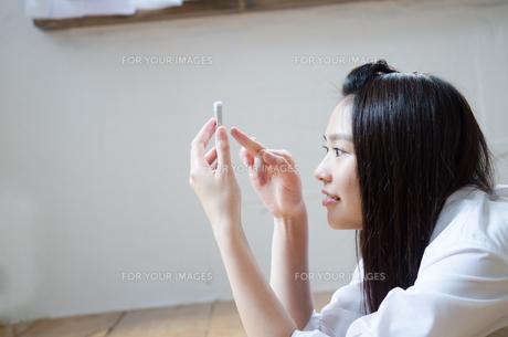イスに座ってスマートフォンを操作する女性の素材 [FYI01077621]