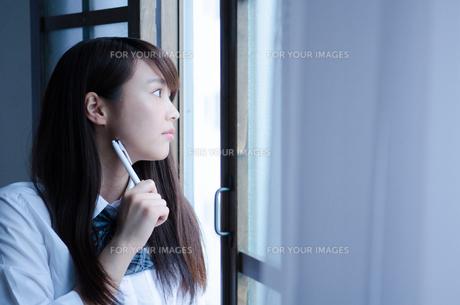 ペンを持って外を眺める制服姿の女性の素材 [FYI01077624]