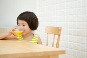 テーブルでオレンジジュースを飲んでいる女の子の素材 [FYI01077626]