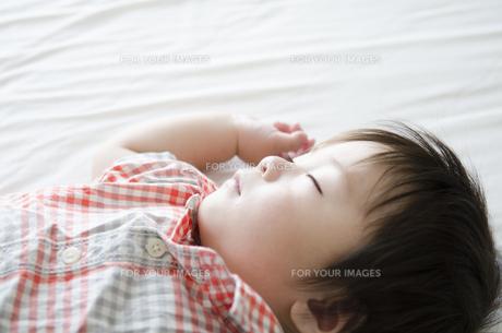 シーツの上で眠る男の子の素材 [FYI01077627]