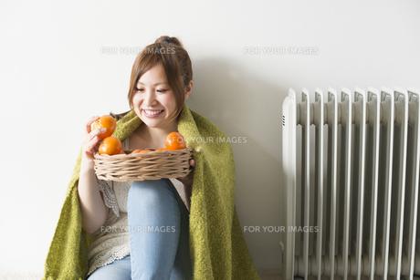 緑の毛布にくるまってみかんを眺める女性の素材 [FYI01077630]