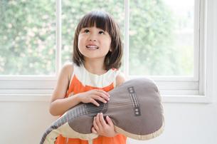 ギターのクッションを持っている女の子の素材 [FYI01077631]