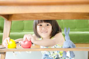机の下で遊んでいる女の子の素材 [FYI01077640]
