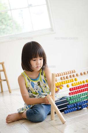 100玉そろばんで遊んでいる女の子の素材 [FYI01077641]