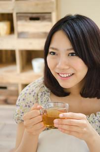お茶の入ったグラスを持って笑う女性の素材 [FYI01077647]