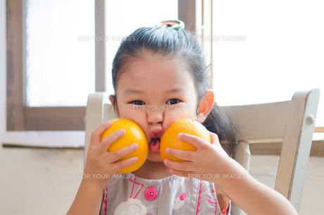 オレンジで顔を挟んでいる女の子の素材 [FYI01077656]
