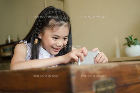 リビングでスマートフォンを操作する女の子の素材 [FYI01077658]