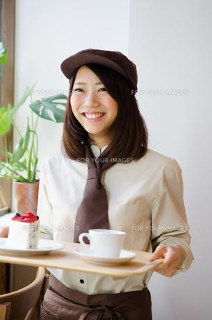 制服を着てカフェで働く女性の素材 [FYI01077659]