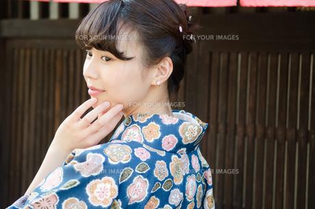 格子の家の前で顔に手を添える着物姿の女性の素材 [FYI01077662]