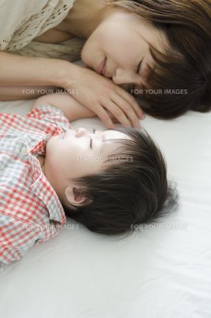シーツの上で眠る男の子とお母さんの素材 [FYI01077665]