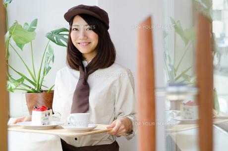 制服を着てカフェで働く女性の素材 [FYI01077668]