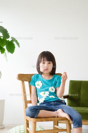 イスに座って何かを食べている女の子の素材 [FYI01077669]