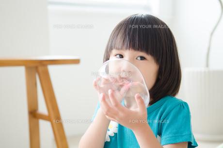 風船を膨らませている女の子の素材 [FYI01077671]
