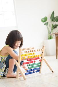 100玉そろばんで遊んでいる女の子の素材 [FYI01077681]