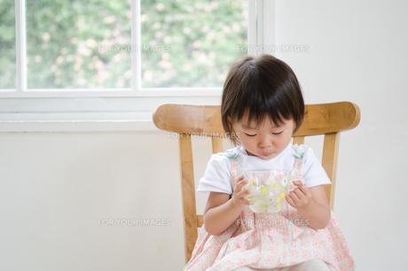イスに座って水の入ったカップを持っている女の子の素材 [FYI01077683]