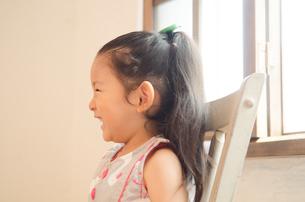 イスに座って笑っている女の子の素材 [FYI01077687]