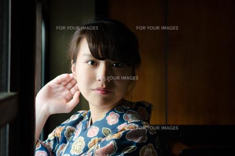日本家屋の窓辺でこちらを見る着物姿の女性の素材 [FYI01077689]
