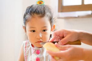 包丁でりんごを切っている手元を見ている女の子の素材 [FYI01077690]