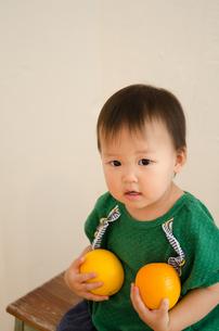 オレンジを両手で持っている女の子の素材 [FYI01077692]