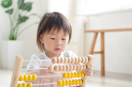 部屋の中で100玉そろばんで遊ぶ女の子の素材 [FYI01077697]