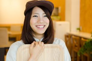 制服を着てカフェで働く笑顔の女性の素材 [FYI01077698]