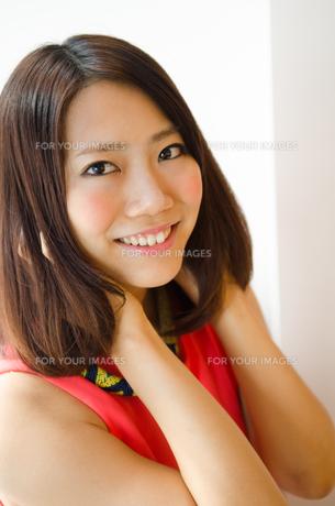 髪を触りながら笑っている女性の素材 [FYI01077701]