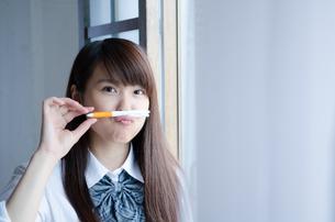 ペンを鼻の下に挟む制服姿の女性の素材 [FYI01077704]