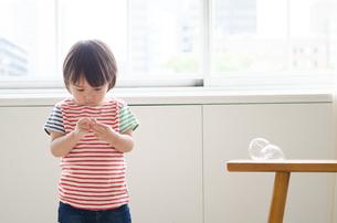 部屋の中で手元を見ている男の子の素材 [FYI01077714]