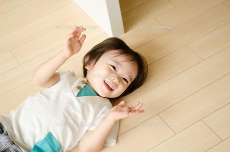床に転がって笑っている男の子の素材 [FYI01077720]