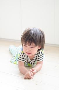 床に這いつくばって泣いている男の子の素材 [FYI01077729]