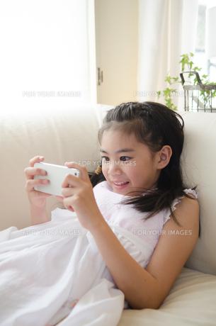 スマートフォンを楽しそうに操作している女の子の素材 [FYI01077733]