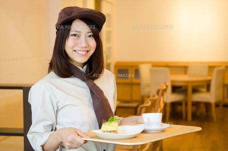 制服を着てカフェで働く女性の素材 [FYI01077737]