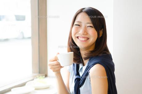 コーヒーカップを持って笑う女性の素材 [FYI01077741]