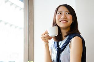 コーヒーカップを持って笑う女性の素材 [FYI01077742]