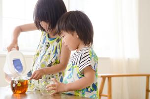 麦茶をついでいる男の子と女の子の素材 [FYI01077756]